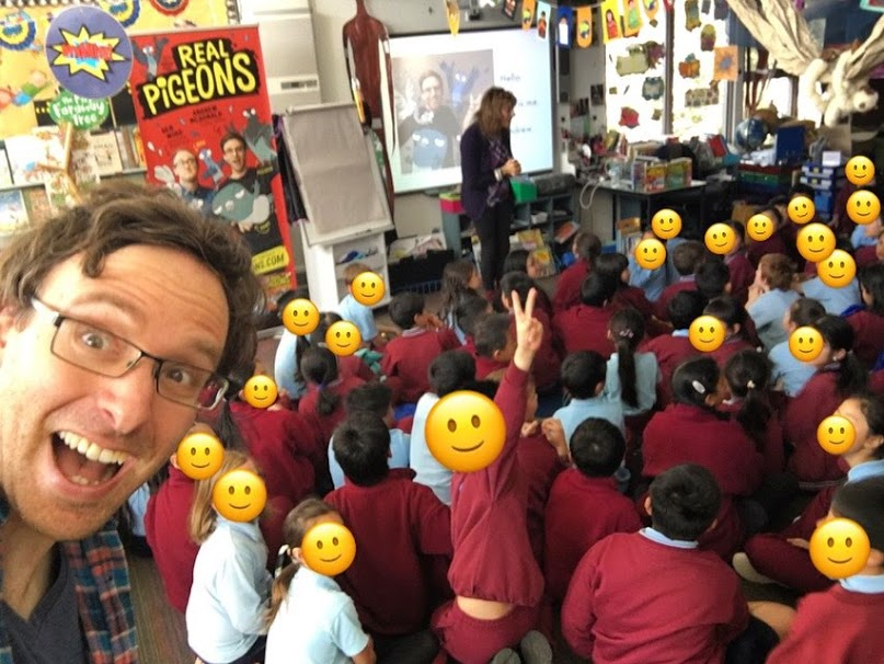 Author Andrew McDonald takes a selfie at a primary school, with school students sitting in the background